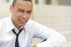 Attractive smiling businessman with a loosened tie. And his collar unbuttoned looking to the right side of the frame, closeup head and shoulders Stock Photo