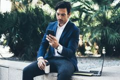 Attractive smiling businessman using contemporary smartphone taking rest during work day.Holding hands take away coffee. Cup.Blurred background. Horizontal Royalty Free Stock Photo
