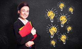 Attractive smiling businesswoman in front of a blackboard with many lightbulbs Royalty Free Stock Image