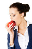 Attractive smiling businesswoman holding red apple Stock Image