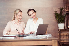 Attractive smiling businesswomen using laptop and taking notes Stock Photo