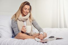Attractive smiling contented young woman reading a magazine. As she relaxes barefoot on her bed with a mug of coffee and a scarf around her neck Stock Images