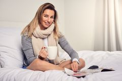 Attractive smiling contented young woman reading a magazine. As she relaxes barefoot on her bed with a mug of coffee and a scarf around her neck Royalty Free Stock Photo
