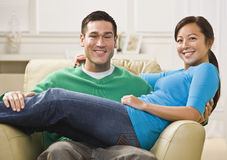 Attractive Smiling Couple on Sofa Stock Images