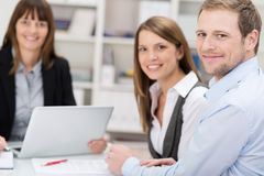 Attractive smiling couple talking to an agent. Or investment adviser sitting at a desk in her office turning to smile at the camera Stock Photos