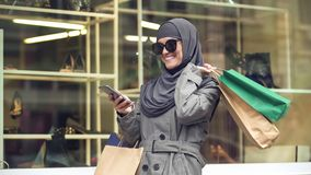 Attractive smiling female in hijab shopping and chatting on phone with friend royalty free stock image