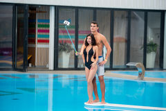 Attractive smiling female posing near swimming pool makes selfie photo with selfie stick and male standing behind her Stock Photos