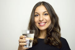 Attractive smiling girl drinking water and looking at camera Royalty Free Stock Image