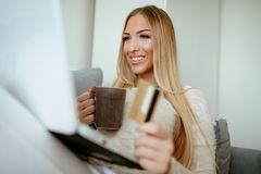 Paying Accounts From Home. Attractive smiling girl sitting at her living room, paying accounts by laptop with credit card and holding cup of coffee. Selective Royalty Free Stock Images