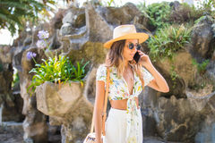 Attractive smiling girl talking on the phone walking in a park in hat and sunglasses. Royalty Free Stock Images
