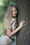 Attractive smiling  girl touching a big tree in a park Royalty Free Stock Images