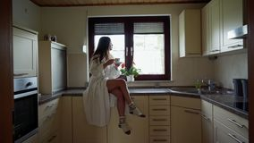 Attractive smiling girl in white bathrobe and wool socks drinks coffee or tea and sitting on the stone table in the cozy. Kitchen at the morning. Beautiful stock video footage