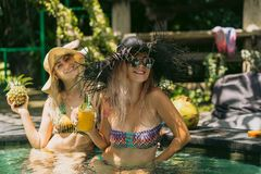 Attractive smiling girls in bikinis holding pineapple and cocktail. In swimming pool stock image