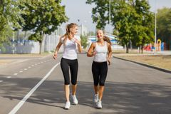 Attractive and smiling girls runners on a park background. Morning jogging. Running concept. Stock Photos