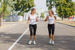 Attractive and smiling girls runners on a park background. Morning jogging. Running concept. Stock Photography