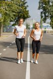 Attractive and smiling girls runners on a park background. Morning jogging. Running concept. Stock Image