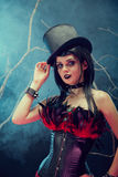 Attractive smiling gothic girl in tophat and feather corset Royalty Free Stock Images