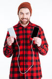 Attractive smiling hipster man charging his mobile phone Royalty Free Stock Image