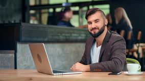 Attractive smiling male businessman posing sitting on table working using laptop at cafe. Medium shot. Portrait of pleasant casual fashion man relaxing enjoying stock video