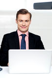 Attractive smiling man operating a laptop Stock Photo