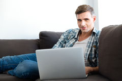 Attractive smiling man sitting on sofa and using laptop Royalty Free Stock Photo