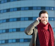 Attractive smiling man talking on mobile phone outdoors Royalty Free Stock Photo