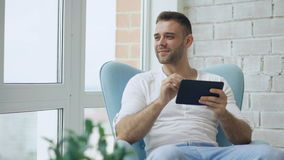 Attractive smiling man using digital tablet sitting in chair at balcony in loft modern apartment stock video footage
