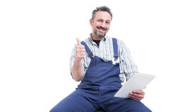 Attractive smiling mechanic showing thumb up gesture Stock Photo
