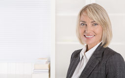 Attractive smiling middle aged businesswoman in portrait wearing Royalty Free Stock Images