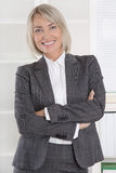 Attractive smiling middle aged businesswoman in portrait wearing Stock Photography