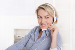 Attractive smiling middle aged woman in blue calling with headse Royalty Free Stock Photography
