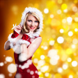 Attractive smiling miss santa. On bokeh background Stock Photos