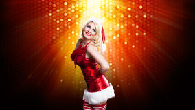 Attractive smiling miss santa. In front of a lights background Stock Photography