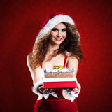 Attractive smiling miss santa. With a present Stock Photo
