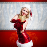 Attractive smiling miss santa. With a present Royalty Free Stock Images
