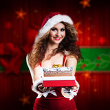 Attractive smiling miss santa with a present. In front of christmas background Royalty Free Stock Photos