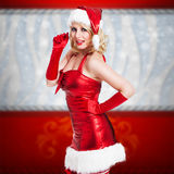 Attractive smiling miss santa. On red background Stock Photos