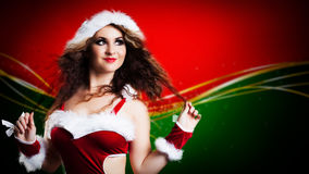 Attractive smiling miss santa. On red background Stock Photo