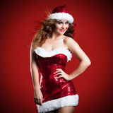 Attractive smiling miss santa. On red background Royalty Free Stock Photography