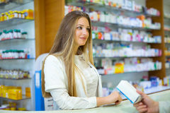 Attractive smiling pharmacist giving her client pills royalty free stock photo