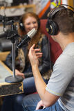 Attractive smiling radio host interviewing a guest Stock Photography