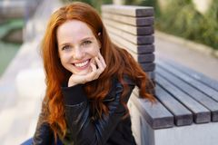 Attractive smiling redhead woman sitting outdoors. On a bench alongside a canal resting her chin on her hand Royalty Free Stock Images