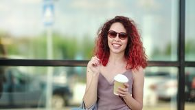Attractive smiling shopaholic redhead young female in sunglasses holding coffee paper cup. At window glass background medium close-up. Beautiful curly happy stock video