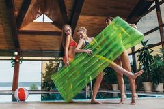 Attractive smiling slim female friends wearing swimsuits holding inflatable lounge posing in spa and wellness center.  stock image