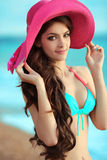 Attractive Smiling teen girl model wearing in fashion pink hat o. N the beach. Summer outdoor portrait. Long curly healthy hair  style Stock Photo