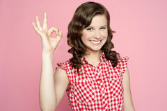 Attractive smiling teenager showing ok sign. Against pink background Royalty Free Stock Image