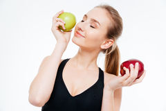 Attractive smiling woman athlete posing with red and green apples. Attractive smiling young woman athlete standing and posing with red and green apples over stock images