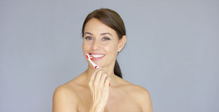 Attractive smiling woman brushing her teeth stock images