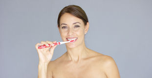 Attractive smiling woman brushing her teeth stock photography