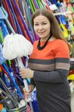 Attractive smiling woman buying new mop in hypermarket store, looking at camera Royalty Free Stock Image